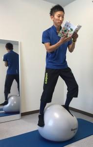バランスボールに立って読書をするバランストレーニング
