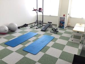 懸垂マシンや腹筋台や診察台が並ぶアスリートルーム